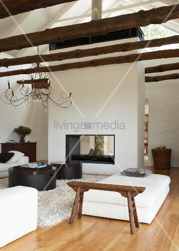 Open fireplace as free-standing partition in open-plan, modern living room with rustic tree trunks as ceiling beams