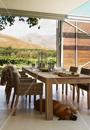 Wooden chairs with wicker seats and hand-crafted, modern wooden table on roofed terrace with amazing view of landscape
