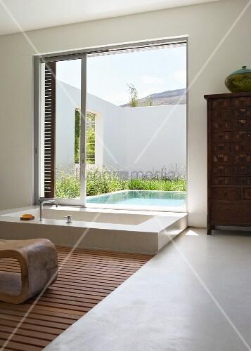 Modern, exotic luxury bathroom - sunken bathtub in front of open sliding terrace door with view of pool in courtyard