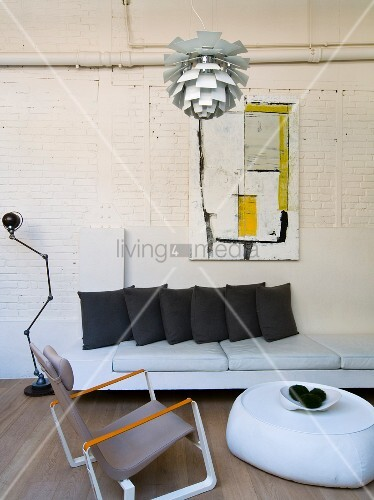 Loft-apartment-style living room with Bauhaus pendant lamp above armchair and ottoman in front of sofa