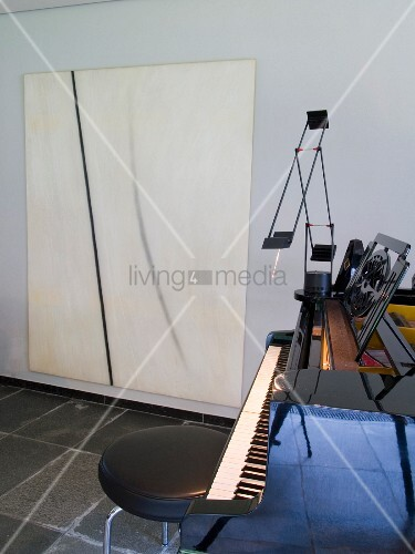 Stool with black leather cover and grand piano with modern artwork on wall behind