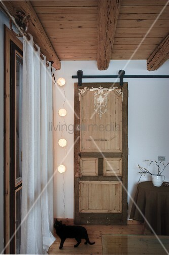 Schwarze Katze Vor Fenster Mit Vorhang Und Rustikaler Schiebetür In  Wohnzimmer Mit Holzdecke