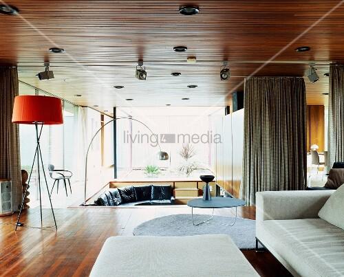 Spacious open-plan living space with light sofa and various Bauhaus-period standard lamps