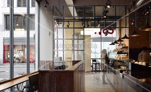 Industrial style in London coffee bar with glass wall and lighting concept using pendant lights and ceiling spots