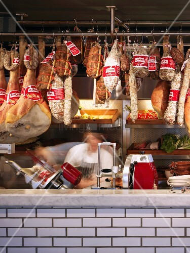 Sausages and hams on butcher's hooks above tiled counter in English shop