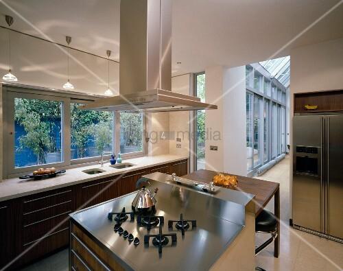 Kochinsel mit Gasherd in Edelstahlfläche und Frühstückstheke mit ...