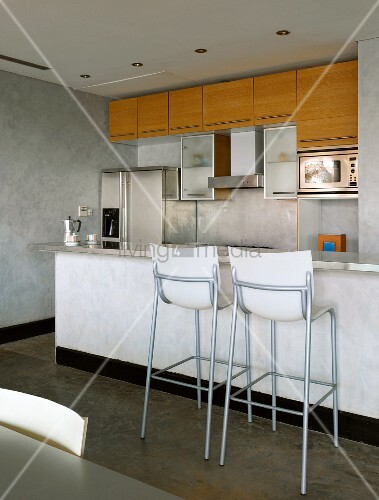 Bar stools in front of counter and concrete walls in open-plan kitchen with glass, wood and stainless steel fronts