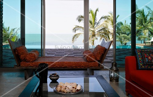 Wooden recamier with loose cushions in front of large windows with view of wooden terrace and palms behind infinity pool