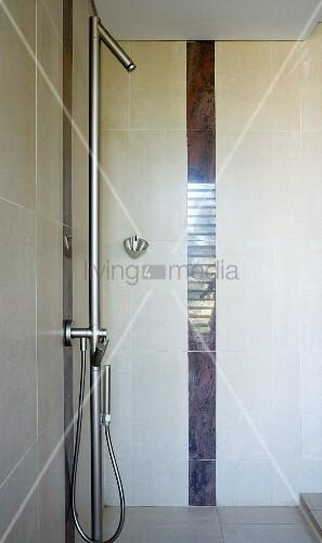 Shower with sunken base, designer fittings and vertical tiling trim in dark marble