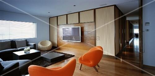 Living room with sofa, orange armchairs & TV