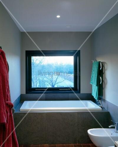 Vor fenster eingebaute badewanne mit grauer fliesenverkleidung bild kaufen living4media - Fenster justieren anleitung mit bildern ...