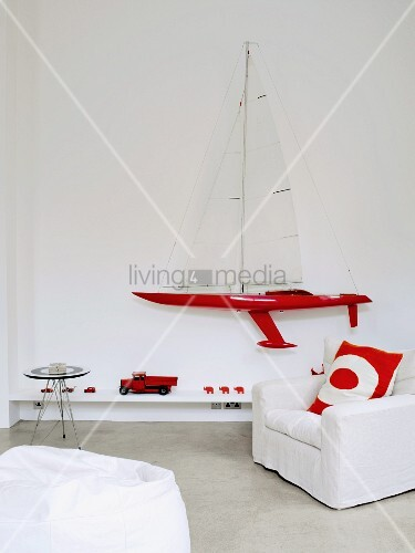 Bright red accessories and model sailing boat on wall combined with white covered chair and beanbag