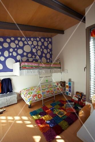 Fröhliches Kinderzimmer Unter Der Dachschräge Mit Buntem Teppich Im  Schachbrettmuster Und Blauer Tapete Mit Großen Weissen