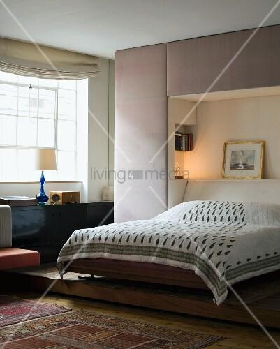 Schlafzimmer mit Bett auf Podest – Bild kaufen – living4media