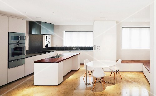 White, stylish, open-plan kitchen with Bauhaus chairs in dining area