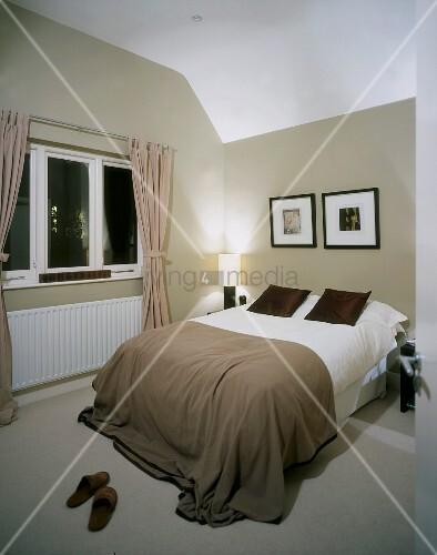 Modernes Schlafzimmer In Gedeckten Naturfarben Mit Schwarz Gerahmten  Bildern über Französischem Bett