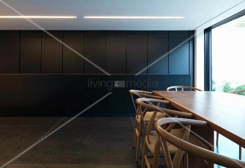 Dining area with classic chairs and monolithic, dark grey kitchen counter
