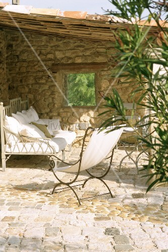Bench and deckchair on roofed terrace with stone wall