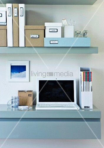 Well organized home office with a sideboard used as a work desk and wall shelving above; storage boxes on top of the shelves in assorted sizes