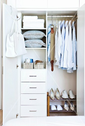Well organized clothes closet with drawers and a shoe rack