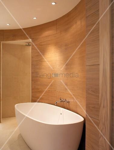 freistehende badewanne vor holzverkleideter wand im ovalen modernen bad bild kaufen. Black Bedroom Furniture Sets. Home Design Ideas
