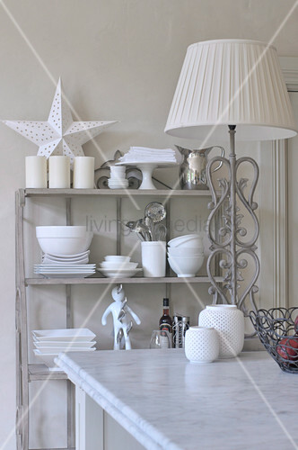 Kitchen table with white marble top and standard lamp in front of shelf of crockery