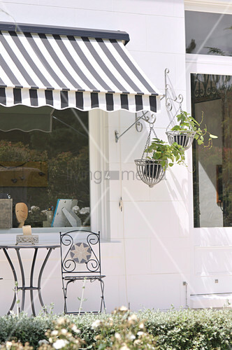 Small table and chair on terrace below black and white striped awning on whitewashed house