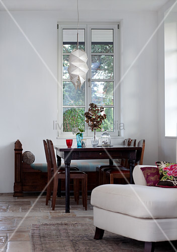 Antique dining table and chairs in front of tall lattice window in living room with stone floor