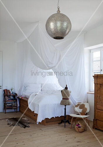 Platform bed with beautifully draped canopy in country house bedroom