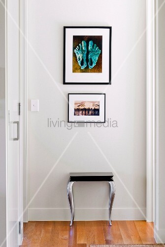Stool below pictures on white wall of hallway