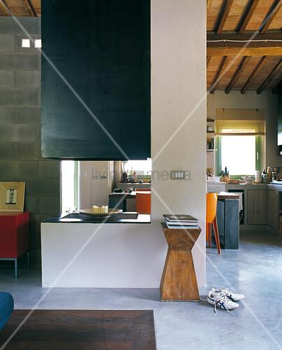 Offener Wohnraum in grünen und blauen Farbtönen unter Dachkonstruktion mit Terrakottaziegeln; in der Mitte ein offener Kamin