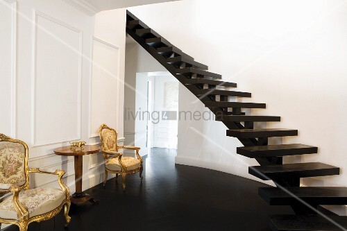Purist, curved, wooden staircase without banisters in a traditional foyer with antique baroque armchairs