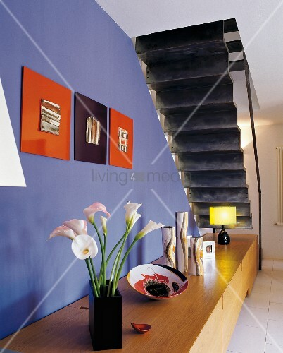 Bouquet on wooden sideboard against wall painted cobalt blue and view of black underside of folded plate staircase in modern setting