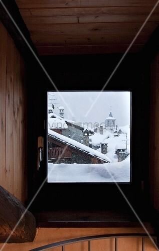 View of snowy roofscape through stairwell window