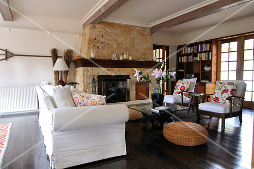 Stone fireplace and upholstered furniture in living room with dark wooden floor