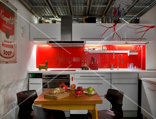 Plain white kitchen units with bright red splashback and red, stylised branches on wall unit doors, industrial ceiling and small dining area with set, wooden table in foreground