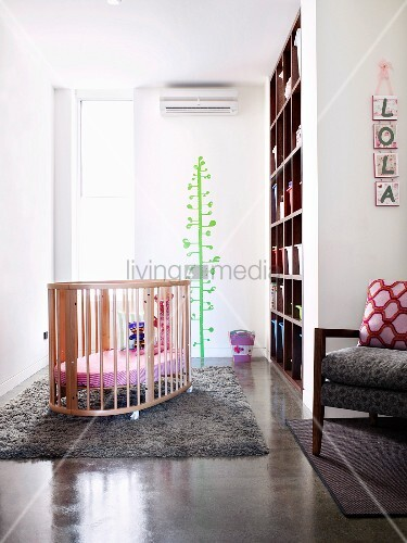 Bright, airy nursery with cot on soft woollen rug and cheerful green tree painted on wall