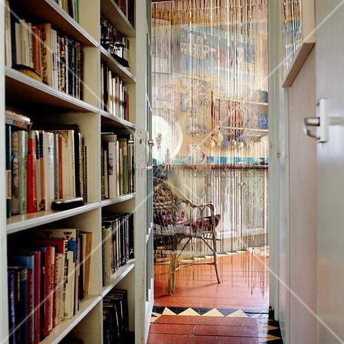 schmaler flur mit eingebautem b cherregal und blick durch offene t r mit fadenvorhang in der. Black Bedroom Furniture Sets. Home Design Ideas