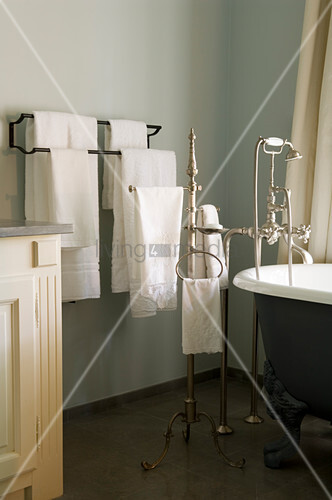 Antike Badewanne mit silberner Armatur und Badetücher in einem ...