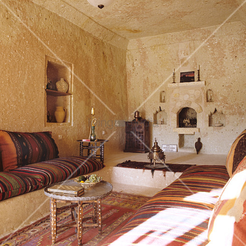 Moroccan interior with striped cushions on masonry platforms and side table of carved wood