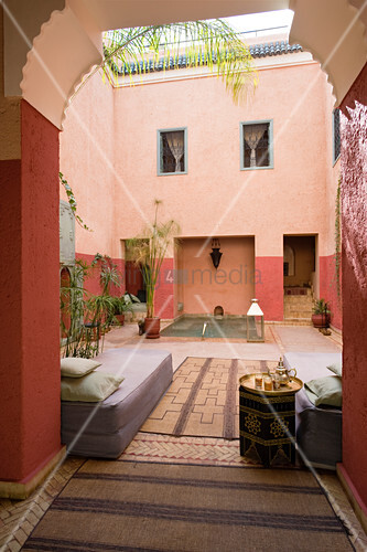 View through a tall gate in a Morrocan courtyard of a day bed and water feature in the back ground