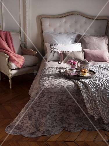 Breakfast tray on comfortable bed with upholstered headboard