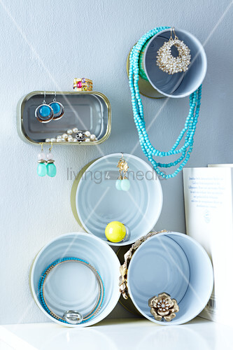 Assorted tin cans on the wall being used a jewelery boxes