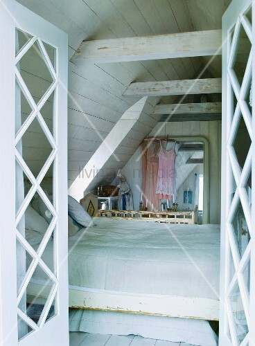 View through open doors of bed in converted attic with wood-panelled walls
