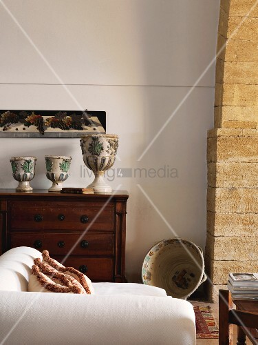 White recamier in front of goblet-shaped vases on antique chest of drawers in Mediterranean interior