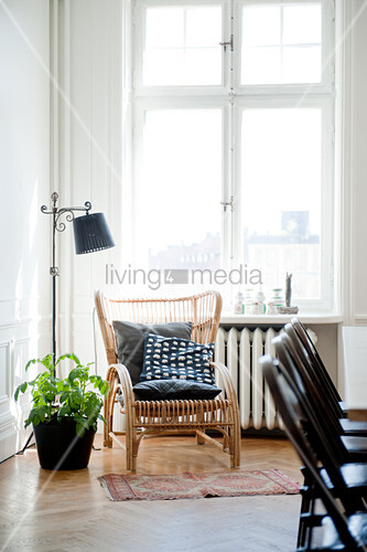 Cushions on wicker chair next to standard lamp below window in corner of living room with traditional ambiance