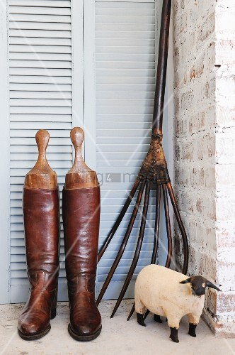 Riding boots, pitchfork and wooden sheep figurine