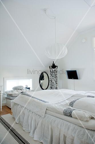 Helles Schlafzimmer in skandinavischem Stil unter dem Dach mit kugelförmiger Hängelampe über Bett