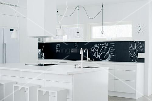 Weisse Designerküche mit schwarzem Spritzschutz; Kochinsel mit Barhockern aus einfachen Holzrahmen