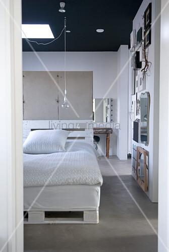 Blick in ein Loft-Schlafzimmer mit schwarzer Decke - ein Selbstbaubett aus weiss gestrichenen Europaletten vor einer Trennwand aus Sichtbeton
